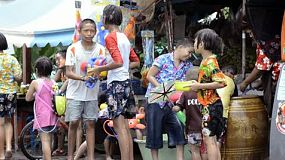 Bangkok, Thailand - April 13, 2012: Children enjoying the annual Songkran festivities with a water fight in the street.  Songkran is traditionally the Thai New Year, and as part of the celebrations, pouring water over other people is done as a way of blessing them. This has escalated to major water fights on the streets, with people pouring water on, or throwing water over anyone who passes by.  [binicons]293727 h 21 icon[/binicons]