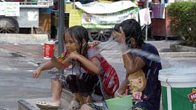 Bangkok, Thailand - April 14, 2014: Three children getting splashed with water during a water fight in the Songkran Festival in Thailand.