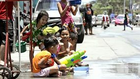 Bangkok, Thailand - April 13, 2012: Children getting showered with water, during the annual Songkran festivities.  Songkran is traditionally the Thai New Year, and as part of the celebrations, pouring water over other people is done as a way of blessing them. This has escalated to major water fights on the streets, with people pouring water on, or throwing water over anyone who passes by.  [binicons]293727 h 21 icon[/binicons]