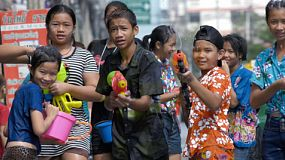 Bangkok, Thailand - April 14, 2014: A group of soaked Thai children with water pistols posing and spraying the camera, as they enjoy the festivities and water fights of the annual Songkran Festival in Bangkok, Thailand.