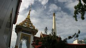 A chimney stack towers over the Buddhist temple before a funeral in rural Thailand.