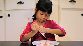 A cute little 6 year old Asian girl adds red icing to her yummy Christmas cookie.