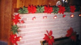 Beautiful Christmas Pointsetta plants surround the fireplace as family and friends get ready to gather around the Christmas tree to open presents on Christmas day in 1967.