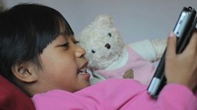 A cute little 8 year old Asian girl reads a story to her teddy bear using her new digital tablet.
