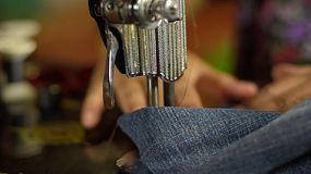 Closeup of a vintage sewing machine sewing the legs of a pair of jeans.
