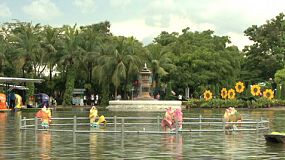 A man talks on his cell phone while he and his date paddle in a colorful paddle boat across a pond in a theme park in Thailand.