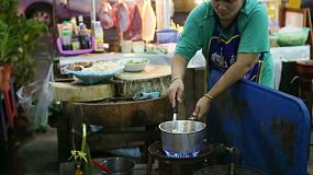 A Thai street food vendor adds the necessary ingredients to a tasty spicy soup at the market in Bangkok, Thailand.