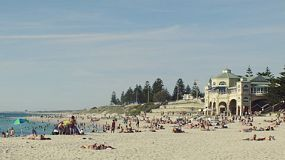 People enjoying relaxing, swimming and sunbathing at Cottesloe Beach in Western Australia, on a hot afternoon.