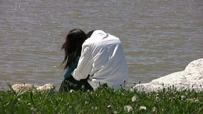 A close up shot of a young couple in love hugging by the waters edge. (HD 1080p30)