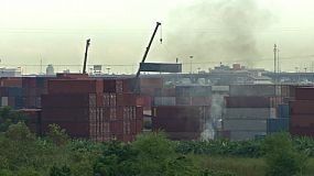 A crane moves a shipping container around while smoke billows from a nearby field.