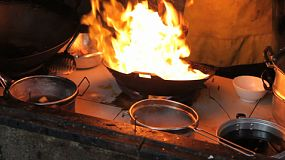 A cook makes delicious Thai food in a wok in northern Thailand even with crazy flames shooting up!