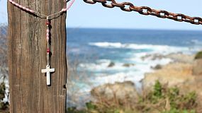 A cross hanging on a fence by the ocean blows in the breeze at Big Sur, California.