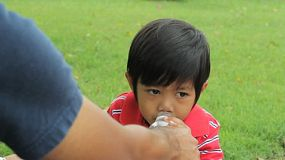 A cute little boy drinks water with his dad at the park in the middle of summer.