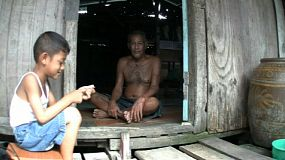 A cute Thai boy sits outside a shack visiting with an old Thai man in the slums of Bangkok, Thailand.