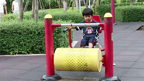 A cute little Asian boy tries out exercise equipment at the local park in Bangkok, Thailand.