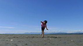 A cute little 9 year old Asian girl enjoys practicing her various gymnastic moves at the beach on a gorgeous sunny summer day.