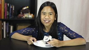 A cute twelve year old Asian girl enjoys eating her delicious chocolate birthday cupcake.