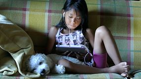 A cute little Asian girl uses her tablet alone in the living room with her faithful puppy at her side.