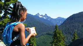 A cute little 12 year old Asian girl pauses in the middle of a mountain hike to enjoy the view and eat a snack on a gorgeous summer day!