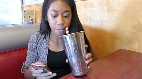 A cute 12 year old Asian girl enjoys sipping on a yummy milkshake.