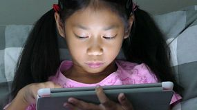 A cute little Asian girl uses her tablet alone in her bedroom at night.