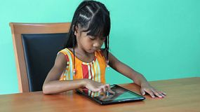 A cute seven year old Asian girl is excited to use her new digital tablet.