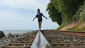 A cute 13 year old Asian girl spends time walking on the railroad track near the ocean on a summer's day!