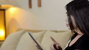 A young asian woman reading on her tablet computer from the comfort of her lounge room.