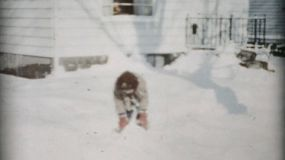 A cute little boy enjoys playing in the snow, and throwing snow balls  in Cleveland, Ohio in 1956.
