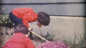 Cute kids enjoy spending time playing in Mom's flower garden and helping out in the summer of 1967.