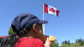 A cute little Asian girl enjoys a yummy hot dog as she celebrates Canada Day in Vancouver.