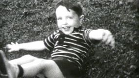 A cute little boy has fun doing somersaults and playing in the front yard in the summer of 1955.