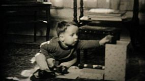 A cute little boy has fun playing with toys and making loud noises in the living room in 1950.