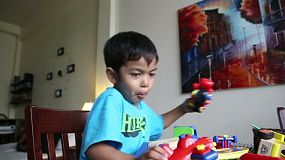 A cute little 4 year old Asian boy has fun playing with his toys at home in Bangkok, Thailand.