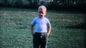 A cute little boy stands in the backyard watching the big kids play games and football in the summer of 1962.
