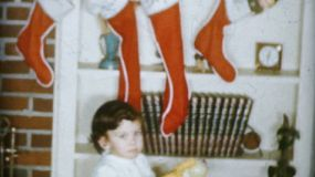 A cute little girl checks out the pretty Christmas stockings on Christmas Day in 1959.