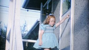 A cute little redhead girl comes down the stairs showing off her pretty new dress as her brother goofs around for the camera in 1966.
