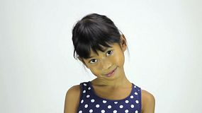 A cute little shy 7 year old Asian girl smiles nervously at the camera.