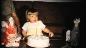 A cute little girl celebrates her first birthday in 1961 by blowing out the candles on her birthday cake in Akron, Ohio.