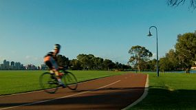 A cyclist passes by while riding on a bike path along the South Perth foreshore.