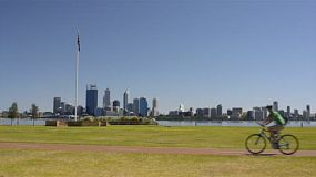 Cyclists riding along a bike path near the edge of the swan river, with perth city, an australian flag and the river in the background. (western australia)