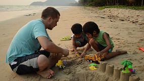 A loving father plays with his two cute Asian boys at the beach while on holidays in Thailand.