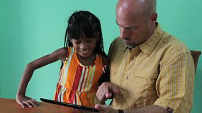 A cute little 7 year old Asian girl hijacks her dad's digital tablet to play some games.