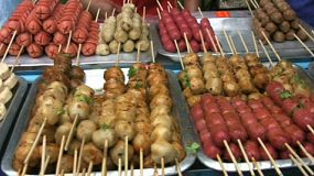 A shot of delicious meat and sausages on skewers being sold at a local market in Bangkok, Thailand.