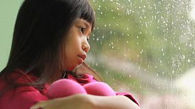 A depressed little seven year old Asian girl sits by a rainy window.