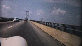 Old antique cars drive over the causeway and the ocean on the way to Ocean City, New Jersey in 1958.