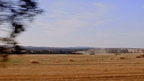 Driving by a field on an Australian farm with a tractor pulling a hay baler, baling square bales of hay .