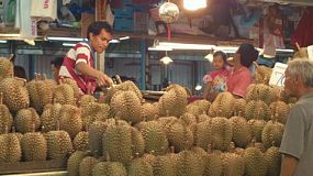 Vendor cutting up durian fruit to sell to a customer at his stall at a Bangkok fruit market in Thailand.
