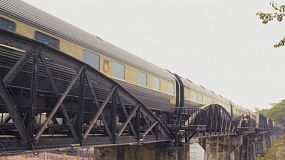 The Eastern & Oriental Express train passing across the famous bridge over the river kwai in Kanchanaburi, Thailand.