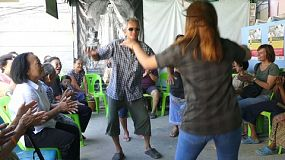 A group of young adults on a short term overseas missions trip have fun teaching action songs to elderly Thai people living in the slums of Bangkok, Thailand.